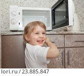 Купить «Веселая девочка стоит около открытой микроволновки», фото № 23885847, снято 29 марта 2015 г. (c) Дарья Филимонова / Фотобанк Лори
