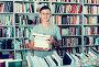 teenage boy with book pile in shop, фото № 23901495, снято 16 сентября 2016 г. (c) Яков Филимонов / Фотобанк Лори