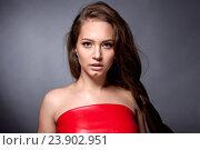 Портрет девушки-подростка в красном платье на сером фоне. Стоковое фото, фотограф Вячеслав Чернявский / Фотобанк Лори