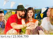 Купить «Happy young couple sitting on grass at camping», фото № 23904799, снято 2 июля 2016 г. (c) Сергей Новиков / Фотобанк Лори