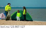 Мать с детьми ставят палатку для семейного отдыха на пляже. Стоковое видео, видеограф Tatiana Kravchenko / Фотобанк Лори