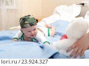 Купить «Малыш в камуфлированной бандане играет лежа на животе», фото № 23924327, снято 23 мая 2015 г. (c) Андрей Некрасов / Фотобанк Лори