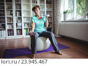 Senior woman exercising with dumbbells on exercise ball. Стоковое фото, агентство Wavebreak Media / Фотобанк Лори