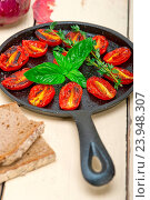 Купить «Oven baked cherry tomatoes with basil and thyme on a cast iron skillet», фото № 23948307, снято 4 ноября 2014 г. (c) easy Fotostock / Фотобанк Лори