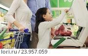 Купить «family weighing paprika on scale at grocery store», видеоролик № 23957059, снято 24 октября 2016 г. (c) Syda Productions / Фотобанк Лори
