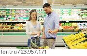 Купить «couple with food in shopping cart at grocery store», видеоролик № 23957171, снято 24 октября 2016 г. (c) Syda Productions / Фотобанк Лори