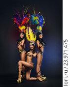 Купить «Молодые девушки в красочных карнавальных костюмах с перьями на темном фоне», фото № 23971475, снято 24 января 2015 г. (c) Евгений Захаров / Фотобанк Лори