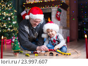 Купить «Father and his son play with model railway near christmas tree», фото № 23997607, снято 16 января 2016 г. (c) Оксана Кузьмина / Фотобанк Лори