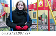Купить «Женщина в пальто сидит на качелях на детской площадке и смотрит в камеру», видеоролик № 23997727, снято 30 октября 2016 г. (c) Кекяляйнен Андрей / Фотобанк Лори