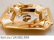 Купить «Золотые обручальные кольца жениха и невесты лежат на подносе на столе в ЗАГСе», эксклюзивное фото № 24082959, снято 15 октября 2016 г. (c) Игорь Низов / Фотобанк Лори