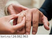 Купить «Невеста надевает золотое обручальное кольцо на палец жениху в ЗАГСе», эксклюзивное фото № 24082963, снято 15 октября 2016 г. (c) Игорь Низов / Фотобанк Лори