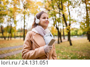 woman with smartphone and earphones in autumn park. Стоковое фото, фотограф Syda Productions / Фотобанк Лори