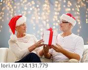 Купить «happy senior couple in santa hats with gift box», фото № 24131779, снято 21 августа 2014 г. (c) Syda Productions / Фотобанк Лори