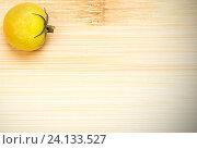 Купить «Маленький зелёный помидор лежит на бамбуковой деревянной доске», фото № 24133527, снято 4 ноября 2016 г. (c) Анна Рахимова / Фотобанк Лори