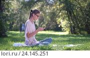 Молодая женщина слушает музыку и использует смартфон в парке. Стоковое видео, видеограф Станислав Толстнев / Фотобанк Лори