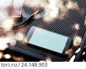 Смартфон с пустым экраном на решетке колонки. Стоковое фото, фотограф ouh_desire / Фотобанк Лори