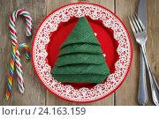 Купить «Салфетка сложенная в форме рождественской елки в красной тарелке. Праздничная сервировка», фото № 24163159, снято 6 ноября 2016 г. (c) Сергей Чайко / Фотобанк Лори