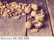 Купить «Walnut kernels and whole walnuts on rustic old wooden table», фото № 24165439, снято 14 февраля 2016 г. (c) Майя Крученкова / Фотобанк Лори