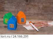Купить «Три разноцветных дома и деньги на дощатом фоне», фото № 24166291, снято 8 ноября 2016 г. (c) Наталья Осипова / Фотобанк Лори