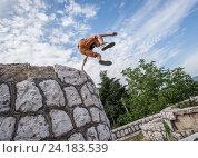 Young boy praticing parkour in Vraca Memorial Park, Sarajevo, Bosnia and Herzegovina. (2015 год). Редакционное фото, фотограф Konrad Zelazowski / age Fotostock / Фотобанк Лори
