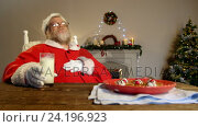 Купить «Santa claus relaxing on chair and having sweet food», видеоролик № 24196923, снято 9 июля 2020 г. (c) Wavebreak Media / Фотобанк Лори