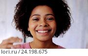 Купить «smiling african american woman touching her hair», видеоролик № 24198675, снято 6 ноября 2016 г. (c) Syda Productions / Фотобанк Лори