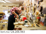 Купить «carpenter with drill drilling plank at workshop», фото № 24206983, снято 14 мая 2016 г. (c) Syda Productions / Фотобанк Лори