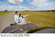 Купить «happy man and woman with road map on car hood», фото № 24206999, снято 12 июня 2016 г. (c) Syda Productions / Фотобанк Лори