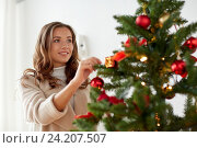 Купить «happy young woman decorating christmas tree», фото № 24207507, снято 15 октября 2016 г. (c) Syda Productions / Фотобанк Лори