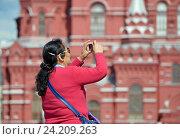 Купить «Иностранная туристка фотографирует на мобильное устройство Исторический музей на Красной площади в Москве», эксклюзивное фото № 24209263, снято 10 июня 2016 г. (c) Александр Замараев / Фотобанк Лори