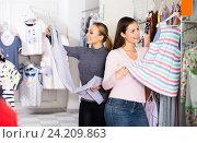 Купить «Two cheerful women selecting sleeping clothes», фото № 24209863, снято 26 июня 2019 г. (c) Яков Филимонов / Фотобанк Лори