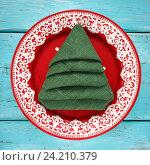 Купить «Салфетка сложенная в форме рождественской елки в красной тарелке, вид сверху. Праздничная сервировка», фото № 24210379, снято 6 ноября 2016 г. (c) Сергей Чайко / Фотобанк Лори