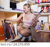 Купить «Young woman customer selecting vibrator in store», фото № 24210859, снято 23 марта 2019 г. (c) Яков Филимонов / Фотобанк Лори