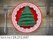 Купить «Салфетка сложенная в форме рождественской елки в красной тарелке. Праздничная сервировка», фото № 24212647, снято 6 ноября 2016 г. (c) Сергей Чайко / Фотобанк Лори