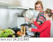 Купить «Little girl and mother at home kitchen», фото № 24212843, снято 20 ноября 2019 г. (c) Яков Филимонов / Фотобанк Лори