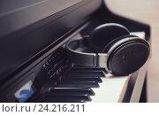 Наушники на фортепианной клавиатуре. Стоковое фото, фотограф Standard Primitive / Фотобанк Лори