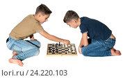 Купить «Мальчики играют в шахматы на белом фоне», фото № 24220103, снято 17 сентября 2019 г. (c) Дмитрий Чемерик / Фотобанк Лори
