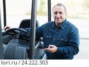 Купить «Worker goes driving loader», фото № 24222303, снято 12 октября 2016 г. (c) Яков Филимонов / Фотобанк Лори