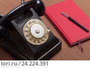 Черный ретро телефон и красный блокнот. Стоковое фото, фотограф Евгений Пидеркин / Фотобанк Лори
