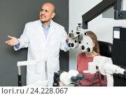 Купить «Ophthalmologist and woman checking eyesight», фото № 24228067, снято 20 июля 2018 г. (c) Яков Филимонов / Фотобанк Лори