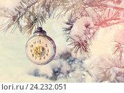 Купить «Новогодний фон  - новогодняя старинная игрушка в виде часов, показывающих канун Нового года, на ветке заснеженной елки», фото № 24232051, снято 5 января 2016 г. (c) Зезелина Марина / Фотобанк Лори