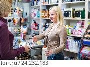 Купить «Positive client at shop paying at cash register», фото № 24232183, снято 23 сентября 2018 г. (c) Яков Филимонов / Фотобанк Лори