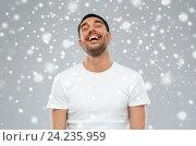 Купить «happy laughing man over snow background», фото № 24235959, снято 15 января 2016 г. (c) Syda Productions / Фотобанк Лори