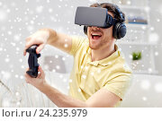 Купить «man in virtual reality headset with controller», фото № 24235979, снято 12 марта 2016 г. (c) Syda Productions / Фотобанк Лори