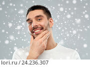 happy young man touching his face or beard. Стоковое фото, фотограф Syda Productions / Фотобанк Лори