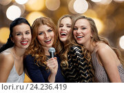 Купить «happy young women with microphone singing karaoke», фото № 24236419, снято 21 ноября 2015 г. (c) Syda Productions / Фотобанк Лори