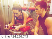 young woman with trainer exercising on gym machine, фото № 24236743, снято 30 ноября 2014 г. (c) Syda Productions / Фотобанк Лори