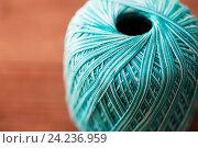 Купить «close up of turquoise knitting yarn ball on wood», фото № 24236959, снято 20 октября 2016 г. (c) Syda Productions / Фотобанк Лори