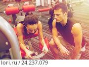 Купить «young woman with trainer exercising on gym machine», фото № 24237079, снято 30 ноября 2014 г. (c) Syda Productions / Фотобанк Лори