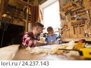 happy father and son with blueprint at workshop, фото № 24237143, снято 14 мая 2016 г. (c) Syda Productions / Фотобанк Лори